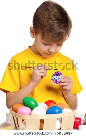 Cute little boy painting Easter eggs isolated on white background