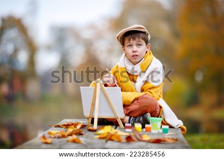 Cute little boy painting in golden autumn park on beautiful autumn day - stock photo