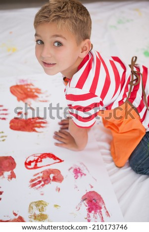 Cute little boy painting on floor in classroom at the nursery school - stock photo