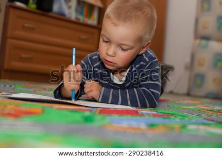 Cute, little boy paints a colorful picture (Shallow DOF). - stock photo
