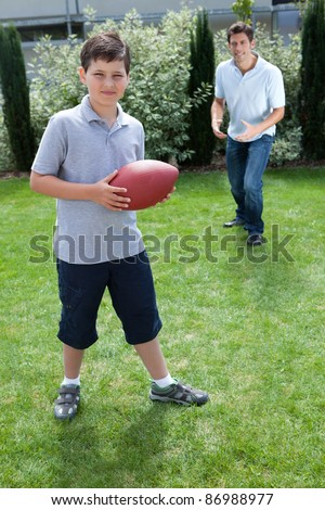 Cute little boy playing american football with his father - stock photo