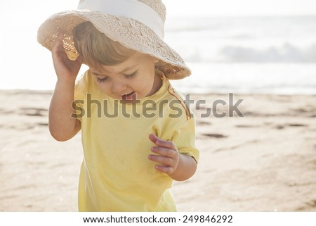 cute little boy playing at the beach with mom's summer hat - stock photo