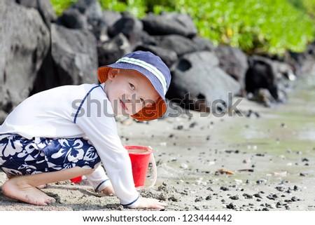 cute little boy playing at the big island beach - stock photo