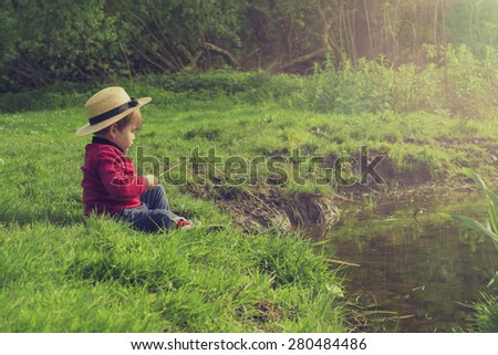 cute little boy playing by the pond - stock photo
