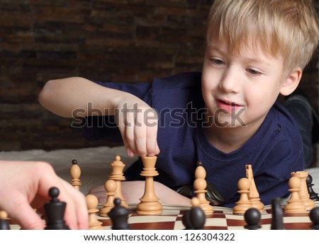 Cute little boy playing chess - stock photo