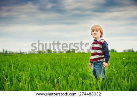 Cute little boy playing in the green field on a cloudy day, wearing pullover, toned image  - stock photo