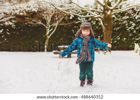 Cute little boy playing in winter park. Kid having fun outdoors, running on snow, wearing warm blue jacket, hat and scarf