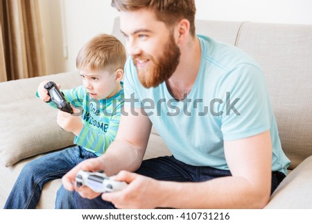 Cute little boy playing video games with his dad sitting on sofa at home - stock photo