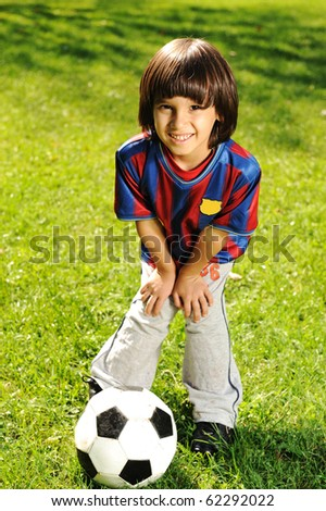Cute little boy playing with a ball in beautiful park in nature - stock photo