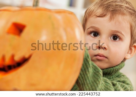 Cute little boy playing with a pumpkin for Halloween - stock photo