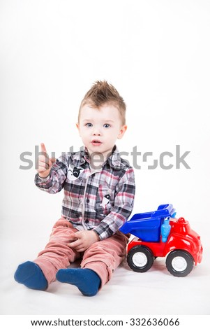 Cute little boy  playing with a toy car. Happy kid sitting isolated on white background.