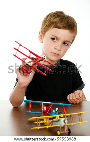 Cute Little Boy Playing with Old Fashioned Airplanes - stock photo