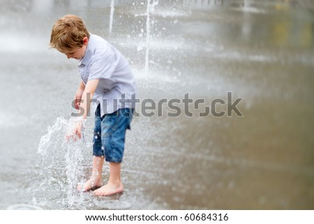 Cute little boy playing with water outdoors on summer day