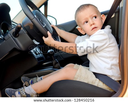 Cute little boy pretending to drive strapped in securely to the drivers seat of a car with his hands on the wheel - stock photo