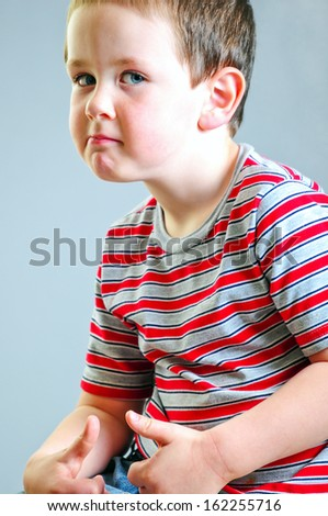 Cute little boy putting on his best tough guy look against a grey background. - stock photo
