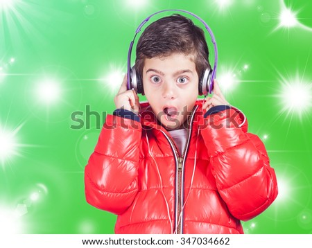 Cute little boy reacts while listening to music. Cross processed image - stock photo
