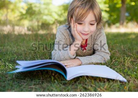 Cute little boy reading in park on a sunny day - stock photo