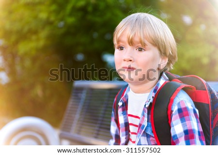 Cute little boy resting on the bench after school, wearing backpack - stock photo