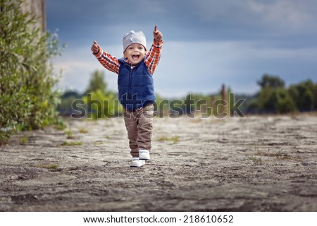 Cute little boy running and smiling with hands up