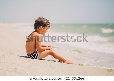 Cute little boy sitting at ocean beach - stock photo