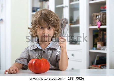Cute little boy sitting at the table unhappy with his vegetable meal. Bad eating habits, nutrition and healthy eating concept.
