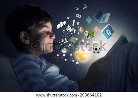 Cute little boy sitting in bed and using tablet pc - stock photo