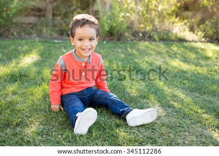Cute little boy sitting in the grass outside - stock photo