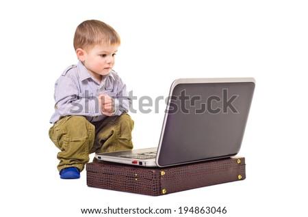 Cute little boy sitting near a laptop - stock photo