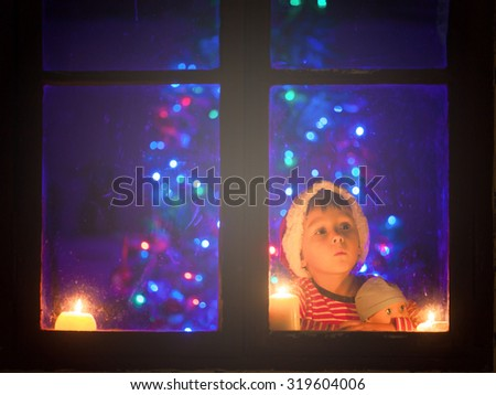 Cute little boy, sitting on a window at night, looking outdoors, waiting for Santa Claus and Christmas, holding a toy, foggy blue filter applied - stock photo
