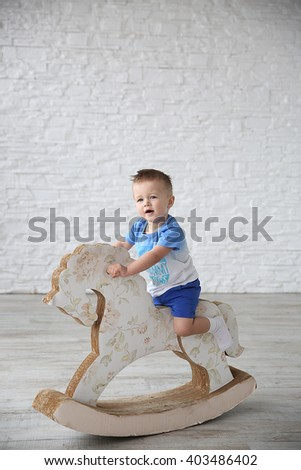 Cute little boy sitting on a wooden toy horse on the background of white brick wall - stock photo