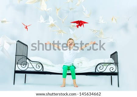 Cute little boy sitting on his bed surrounded by paper birds. Dream world. - stock photo