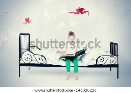 Cute little boy sitting on the bed and reading fairy tales. Dream world. - stock photo
