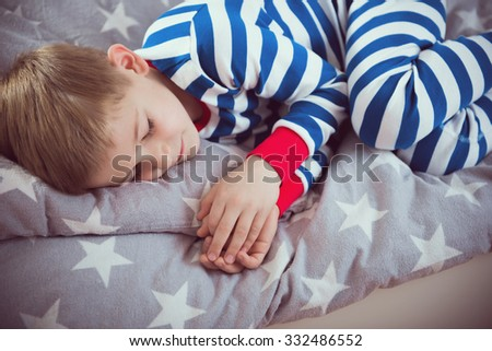 Cute little boy sleeps in striped pajamas on bed. View from above