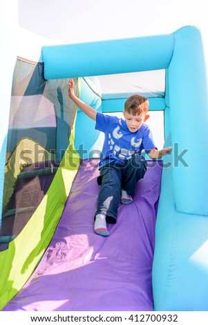 Cute little boy sliding down blue and purple inflatable outdoor carnival amusement ride - stock photo