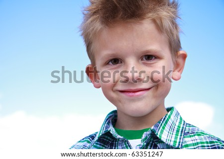 Cute little boy smiling at the viewer and wearing stripes on a white background