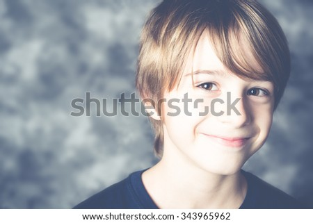 cute little boy smiling on gray background speckled - stock photo