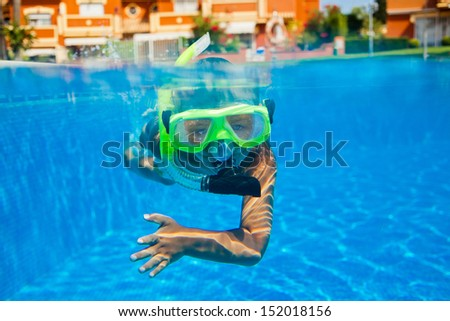 Cute little boy swimming underwater in the pool