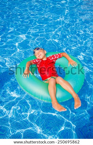 Cute little boy swims in a pool in an green life preserver