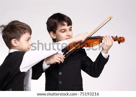 cute little boy teaching his friend to play a violin - stock photo