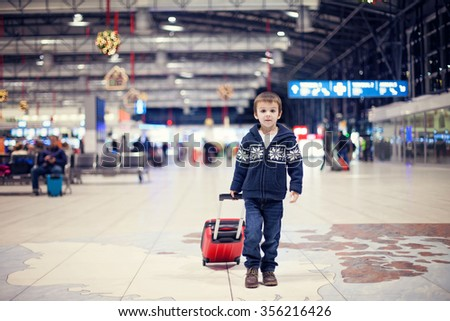 Cute little boy, traveling home for the holidays, Christmas time, waiting happily for the plane to departure - stock photo