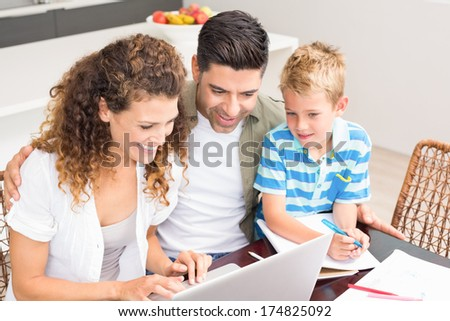 Cute little boy using laptop with his parents at table at home in kitchen - stock photo