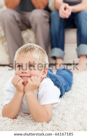 Cute little boy watching television lying on the floor at home