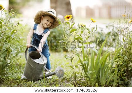 cute little boy watering flowers watering can - stock photo