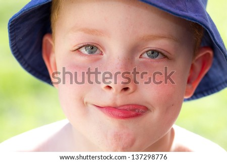 cute little boy wearing a sun hat in the garden sticking out tongue - stock photo