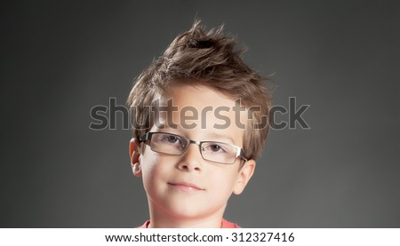 Cute little boy wearing glasses. Studio shot portrait over gray background. Fashionable little boy.
