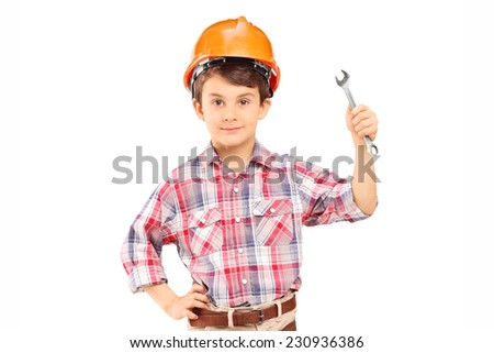 Cute little boy wearing working clothes and holding a wrench isolated on white background - stock photo