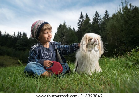 Cute little boy with a cap cuddling his dog in nature - stock photo