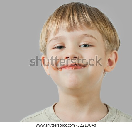 cute little boy with a chocolate on the face - stock photo