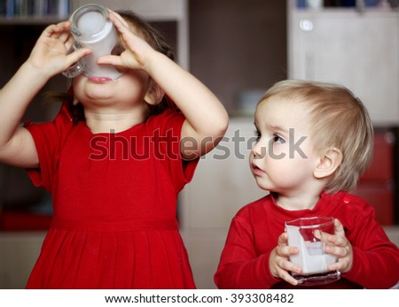 Cute little boy with a glass of milk looking at her sister drinking a glass of milk at home, food and drink concept, healthy food, indoor - stock photo