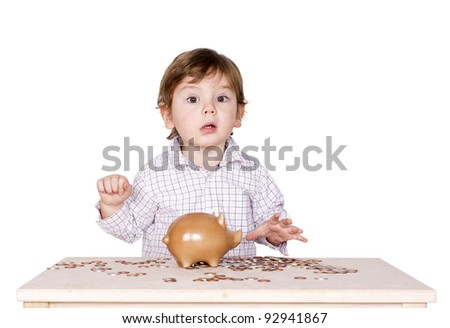 Cute little boy with a piggy bank and some coins on the table. - stock photo
